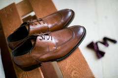 Shoes stacked in composition on a black desk. Groom Accessories: belt, wooden Butterfly, watches, cufflinks and shoes stacked in composition on a black desk Stock Photo