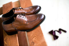 Shoes stacked in composition on a black desk. Groom Accessories: belt, wooden Butterfly, watches, cufflinks and shoes stacked in composition on a black desk Stock Images