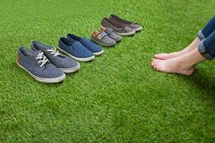 Shoes standing  on grass in front of bare legs Stock Photo
