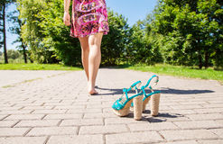 Shoes standing on sidewalk and female legs going away Stock Photography