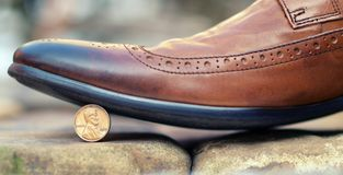 Shoes stopped the coin as a symbol of thrift and savings. Brown leather shoe stepping on a coin standing on edge - 1 cent with the image of Lincoln Royalty Free Stock Photos