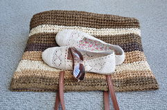 Shoes and sunglass over straw bag Royalty Free Stock Image