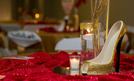 Shoes On A Table. Beautiful Red Table Setup With a sparkling gold shoe, accented by a group of candles in vases Stock Image