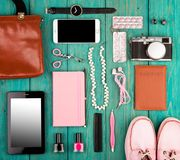 Shoes, tablet pc, smart phone, camera, headphones, bag, notepad, watch, passport and essentials on blue wooden desk. Travel concept - shoes, tablet pc, smart Royalty Free Stock Photos
