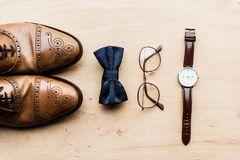 Shoes, tie bow with glasses and watch on wooden floor. Top view of shoes, tie bow with glasses and watch on wooden floor Royalty Free Stock Photography