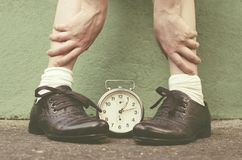 Shoes in time with retro style. Old shoes and an old alarm clock describe the vintage period when time passed slowly Royalty Free Stock Image