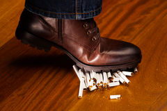 Shoes trampling down on cigarettes Royalty Free Stock Photo