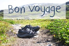 Shoes On Trekking Path, Bon Voyage Means Good Trip. French Text Bon Voyage Means Good Trip. Trekking Shoes On Hiking Path In Norway. Mountains In The Background Royalty Free Stock Image