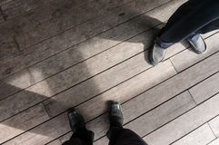 Shoes of two employee standing on Plank Royalty Free Stock Images