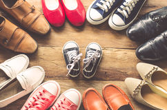 Shoes various styles with children`s shoes. In the middle on a wooden floor - the concept of family care stock photos