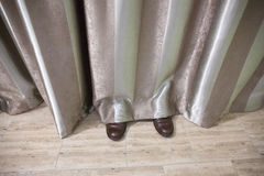 Shoes Visible Behind and Under Curtains Stock Photo