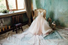 Shoes and wedding dress on chair in room.  Stock Image