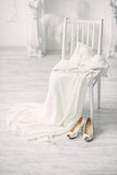 Shoes and wedding dress on chair in room Stock Photos