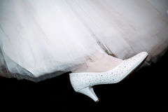 Shoes white of the bride on her leg. Royalty Free Stock Photography