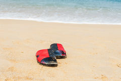 Shoes on white sand beach in day noon light Stock Photos