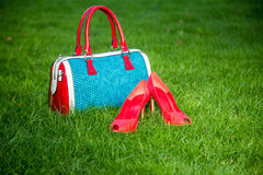 Shoes and women's handbag lay on the grass, women's shoes Royalty Free Stock Photos