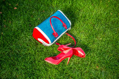 Shoes and women's handbag lay on the grass, women's shoes. A Royalty Free Stock Photos