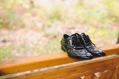 Shoes on Wooden Fence. Black shoes on wooden fence at porch Royalty Free Stock Photography