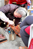 Shoeshine woman. Older woman polish shoes in the street of amoy city, china. she was older, while significant, but she is very dedicated, very impressive