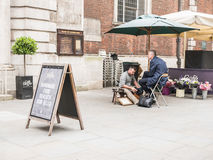 Shoeshine worker offers shine to man outside St Mary le Bow chur Royalty Free Stock Image
