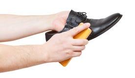 Shoeshiner brushing black shoe by brush Stock Image