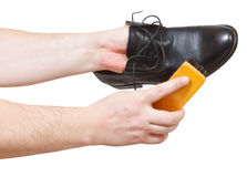 Shoeshiner cleaning black shoes by brush Stock Image