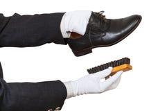 Shoeshiner in den weißen Handschuhen, die schwarze Schuhe säubern Lizenzfreie Stockfotografie