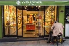 Shoeshiner polerande skor framme av det lokala Yves Rocher lagret med dess tecken Yves Rocher är ett franskt skönhetsmedelmärke arkivbilder