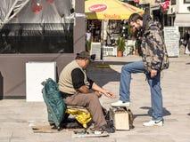 Shoeshiner som polerar skorna av en vit ung man i den Skopje bazaren i huvudstaden av Makedonien royaltyfri fotografi