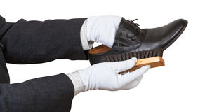 Shoeshiner in white gloves brushing black shoe Stock Photography