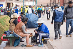 Shoeshiner working in Cusco street, Peru Royalty Free Stock Images