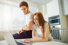 Shoked couple with open mouth on line with laptop in living room in home. Shoked confused couple with open mouth on line with laptop in living room in home Stock Image