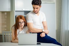 Shoked couple with open mouth on line with laptop in living room in home. Shoked confused couple with open mouth on line with laptop in living room in home Stock Photography