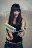 Shoked girl holding tools over grunge background Royalty Free Stock Photo