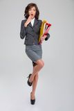 Shoked woman standing on one leg and holding binders. Shoked young curly pretty woman in gray costume standing on one leg in heel shoes and holding binders stock photography