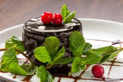 Shololadnoe Cake, decorated with cherries and mint. On a plate with icing sugar and chocolate sauce Royalty Free Stock Photography