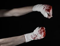 Shook his bloody hand in a bandage, bloody bandage, fight club, street fight, bloody theme, black background, isolated Royalty Free Stock Image