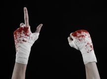 Shook his bloody hand in a bandage, bloody bandage, fight club, street fight, bloody theme, black background, isolated. Studio Stock Images
