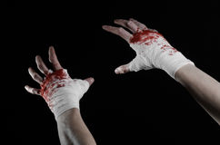 Shook his bloody hand in a bandage, bloody bandage, fight club, street fight, bloody theme, black background, isolated Royalty Free Stock Photo