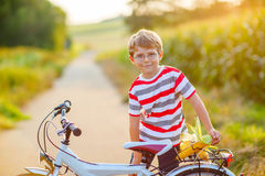 Shool kid boy having fun with riding of bicycle. Happy  school kid boy having fun with riding of bicycle. Active child making sports with bike in nature. Safety Royalty Free Stock Image