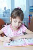 Shoolgirl执行她的家庭作业 免版税库存照片