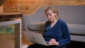 Shooot del primer de la mujer caucásica del eldery que usa el ordenador portátil que se sienta en el piso en el hogar acogedor de metrajes