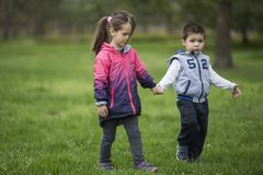 Boy and girl holding hands and walking in nature. Shoot of the Boy and girl holding hands and walking in nature stock photo