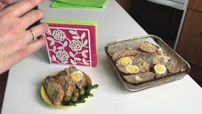 Shoot cooked food on your smartphone. The woman puts on the table a cooked meat roll with a stuffed of boiled eggs, sliced. Makes a composition for shooting stock footage