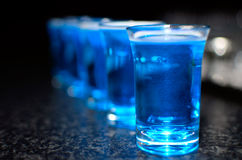 Shoot glasses. With blue drink Stock Photos