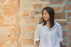 Shoot photo Asian woman portrait wear white shirt and looking sideways with red brick background. Shoot photo Asian woman portrait wear white shirt and looking Stock Photography