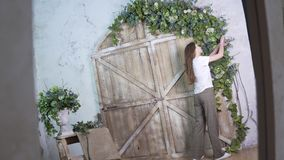 Shoot in reflection, stylish girl florist decorates a beautiful wooden photo zone with flowers stock images
