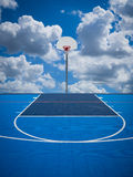 Shoot for the Sky. A basketball court, net and backboard against a blue sky and clouds. Reach for the clouds, shoot for the sky stock images