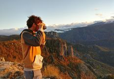 Man taking picture of sunset in mountains Royalty Free Stock Photography