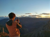 Man taking picture of sunset in mountains Royalty Free Stock Image